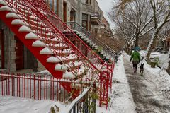 Montreal street in winter. Montreal, CA - 21 November 2018: A woman is walking on a street covered with snow in winter Montreal, Canada stock photography