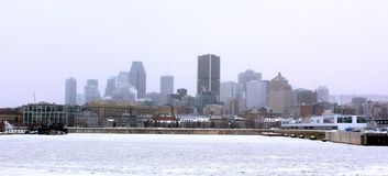 Montreal in winter. Cityscape of Montreal, Quebec, Canada in winter with frozen St Lawrence River on a foggy day stock photography