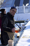 Montreal Winter Fest. Man smiling and happy to be serving maple Taffy on snow Royalty Free Stock Images