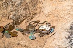Montres de poche cassées et vieilles pièces de monnaie sur une falaise Photos libres de droits