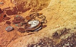 Montres de poche cassées par vintage et vieilles pièces de monnaie sur une falaise Image stock