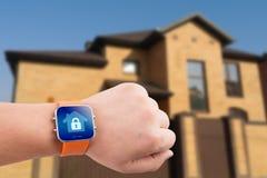 Montres de Smart avec la sécurité à la maison APP sur une main sur le fond de bâtiment photos stock