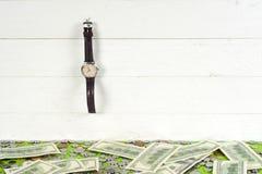 Montres, pièces de monnaie et dollars sur la table en bois Photo stock