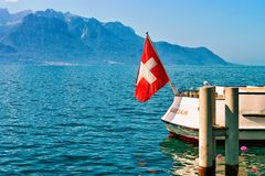 Montreux, Switzerland - August 28, 2016: Boat with Swiss flag at Geneva Lake in Montreux, Vaud canton, Switzerland. Montreux, Switzerland - August 28, 2016: Boat stock photo