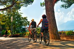 Montreux, Switzerland - August 28, 2016: Couple riding a bicycle on the embankment of Geneva Lake in Montreux, Swiss Riviera. Montreux, Switzerland - August 28 royalty free stock images