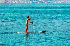 Montreux, Switzerland - August 28, 2016: Girl standing on standup paddle surfing in Geneva Lake in Montreux, Switzerland. Montreux, Switzerland - August 28, 2016 stock images