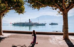 Montreux, Switzerland - Vintage boats in lake Geneva and kid with kick scooter. SEP 25, 2013 Montreux, Switzerland - Vintage sightseeing boats in lake Geneva and stock photos