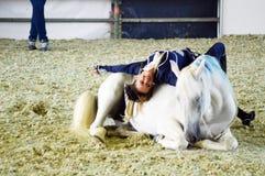 Montrez que la femme jockey spectaculaire de femme de mouvement dans le costume bleu tourne sur un cheval blanc Exposition intern Photo stock