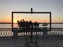 Monument 'Lastkahn-Schlepper auf dem Volga 'auf dem Hintergrund des Flusses und des Sonnenuntergangsommerhimmels stockfotos