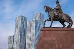 Monument in Astana. Monument to man on horseback against the background of high-rise buildings in Astana Royalty Free Stock Photography