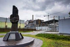 Monument aux liquidateurs de Chernobyl avec le quatrième réacteur sur le fond Photo libre de droits