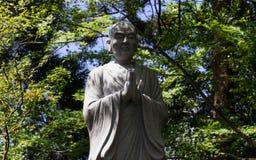 Monument av be, buddistisk munk Gr?n vegetation i bakgrunden arkivfoton