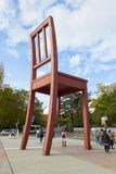 Monument of broken chair. Geneva, Switzerland - October 29, 2017: People visiting the broken chair monument at the Square of Nations in sunny day stock photos