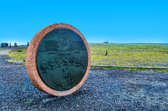 Monument of circle figure. Monument of circle figure from red asphalt stone with black coin-shaped center with engraved drawing. Norway Stock Photography