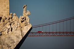 Monument de Lisbonne aux statues d'explorateurs de découvertes avec la 25ème de la passerelle d'avril Photographie stock