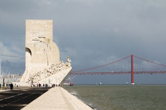 Monument der Entdeckungen und das 25. von April-Brücke, Lissabon, Portugal Lizenzfreie Stockbilder