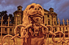 The monument in the form of a lion. With a chain in his mouth against the background of the Palace at night in St. Petersburg royalty free stock photo