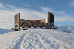 Monument on Georgian Military Road. Snowy mountains and blue sky - Caucasus Mountains, Georgia, near ski resort Gudauri. This sightseeing platform (the monument royalty free stock image