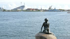 Monument of little mermaid in background of modern cityscape of Copenhagen in sunny day. 4K stock video footage