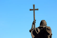 A monument of a man with a cross on sky background Royalty Free Stock Image