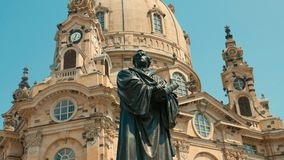 Monument of Martin Luther - the founder of the Reformation. The. Man holds a book in his hands and looks away, dressed in a gown Stock Photo