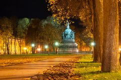 The monument Millennium of Russia in Veliky Novgorod in autumn night and alley of Kremlin park in the autumn night time stock photo
