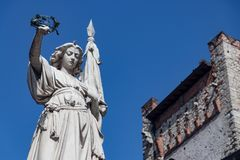 Monument mot den blåa himlen en kvinna som rymmer en krans i hans H arkivbild