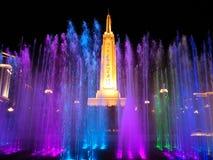 Monument och f?rgrik springbrunn i natten arkivbild