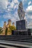 Monument and Orthodox church in Resita, Romania. RESITA, ROMANIA - SEPTEMBER 1, 2016: New monument with the inscription ,,It is sweet and honorable to die for royalty free stock image