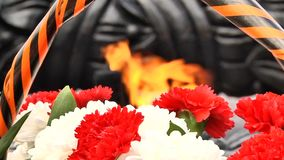 The monument of the Second World War - the eternal flame and flowers. Closeup stock video footage