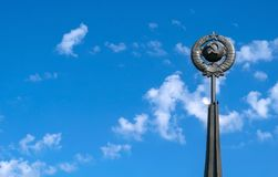 A monument of the Soviet era hammer and sickle on the background of blue sky. Stella, a monument of the Soviet era hammer and sickle on the background of blue stock photography