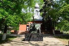 Monument ter ere van overwinning in de Tweede Wereldoorlog Een artilleriekanon en een gebouw met potten van aarde van slagplaatse stock afbeeldingen