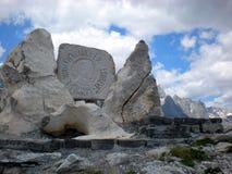 Monument till Edith Durham på Theth, nordliga Albanien, med de albanska fjällängarna i bakgrunden royaltyfri fotografi