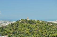 Monument till Philopapos, på överkanten av kullen Philopapos som ses från akropolen av Aten Arkitektur historia, lopp, Landsc royaltyfria foton
