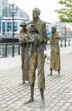 Monument till potatissvälten i Irland tillsammans med floden Liffey i Dublin royaltyfri bild