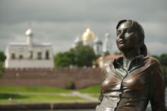 "Monument ""Tired tourist"" in Great Novgorod, Russia. Monument to tourist girl in Veliky Novgorod created by Vadim Borovykh on the blurred background of the Stock Image"