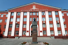 A monument to academician Michael lisavenko on the background of the Altai state agrarian University. BARNAUL, RUSSIA - JULY 2, 2015:A monument to academician Royalty Free Stock Photography