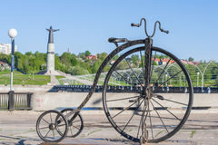 Monument to the bike with a large front wheel on the bay in Cheboksary, Chuvash Republic. Russia. In the background manument patro. Ness mother Royalty Free Stock Photos