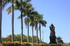 Monument to the deity. Surrounded by palm trees and flowers royalty free stock images