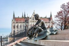 Monument to Hungarian poet Jozsef Attila on Danube embankment with Parliament of Hungary at background, Budapest, Hungary stock photos