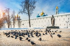 Monument to Sergius of Radonezh at the Lavra. Walls in Sergiev Posad and many pigeons on a winter sunny day Stock Image