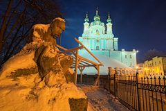 The monument to Taras Shevchenko in the snow and St. Andrew`s Church on a hill at night. Andriyivskyy Descen uzviz. Kyiv. Ukraine Stock Photo