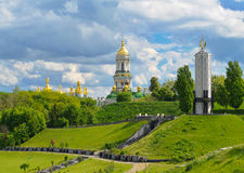 Monument to victims of Holodomor and Kiev-Pechersk Lavra in Kiev. Monument to victims of Holodomor and Domes of Kiev-Pechersk Lavra in Kiev on green hills of Stock Photography