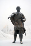Monument to Yuri Dolgorukiy in Dmitrov Kremlin. Moscow region, Russia. The monument is covered by the snow, Kremlin church is seen at background covered by the Royalty Free Stock Photo