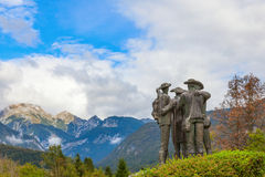 The monument in the town of Ribcev Laz, Slovenia. Sculptural group on the background of mountain peaks and cloudy sky Stock Photography
