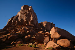 Monument valley. Rock formation of red sand with bush in front in monument valley Stock Images