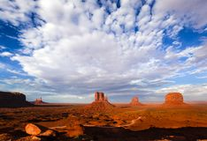 Monument Valley. Famous view of Monument Valley with Mittens and Merrick buttes at sunset. Saddleback meta, Stagecoach and Castle Rock on the left Stock Photos