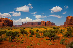 Monument Valley landscape with vegetation and clouds in the blue