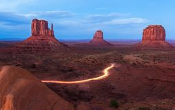 Monument Valley. The Mittens and Merrick Butte after sunset with tourists cars coming back from the scenic driver, a 17 mile unpaved loop road that winds through Royalty Free Stock Image