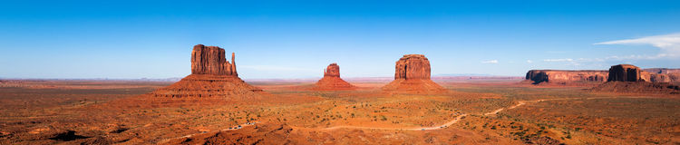 Monument Valley panorama. Big panorama made of multiple images stitched together. Small cars on the bottom of the image give the viewer the real sense of scale